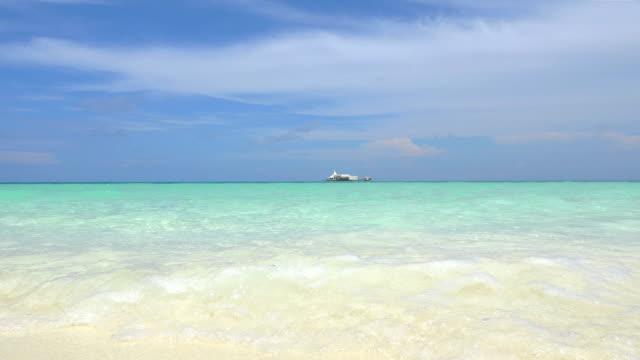 CLOSE UP: Small waves splashing onto beautiful white sand beach video