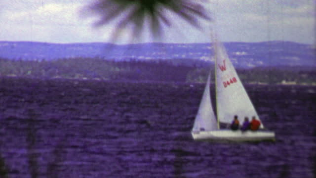 1961: Small white sailboat moving quickly across dark blue waters. . regatta stock videos & royalty-free footage
