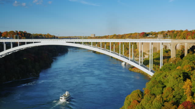 Small white ship sails under the bridge over the river Niagara. Some of the popular Niagara Falls in the US video