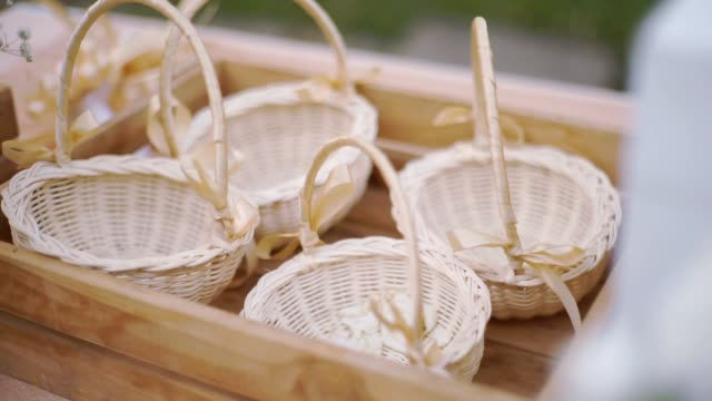 small wicker baskets with ribbons in a wooden tray at outdoor party. - ивовый прут стоковые видео и кадры b-roll
