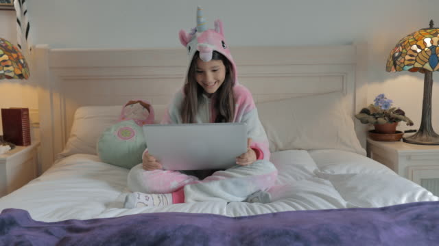 small with unicorn pajamas sitting on white bed makes video conference on gray laptop