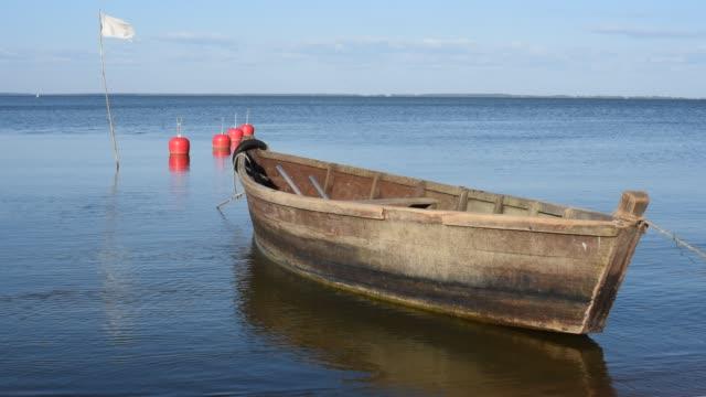 vídeos de stock, filmes e b-roll de pequeno barco de madeira flutuando na água clara - países bálticos