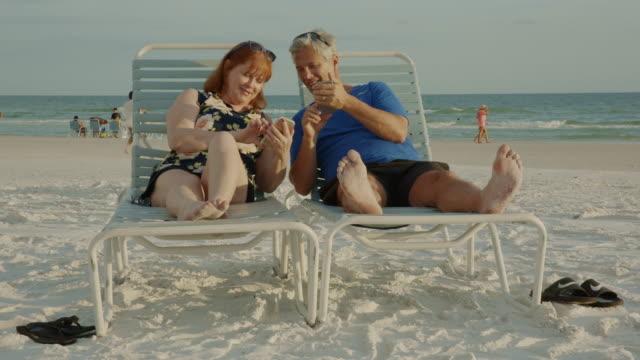 smarphone älteres paar social-media-florida-strand - sun chair stock-videos und b-roll-filmmaterial