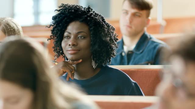 スマートで美しい若い黒女の子待機教室で講義する多民族の学生の完全な。フィールドの浅い深さ。 ビデオ