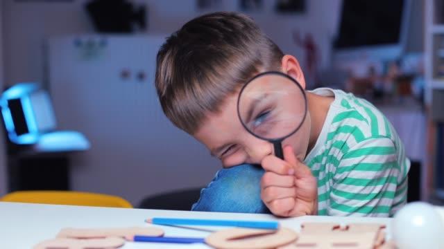 vídeos y material grabado en eventos de stock de chico inteligente mira con un ojo en una lupa - clase de ciencias