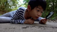istock Smart boy watching ants with magnifying glass 1223622465