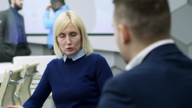intelligente geschäftsfrau etwas männlicher kollege erklärt - haarfarbe stock-videos und b-roll-filmmaterial