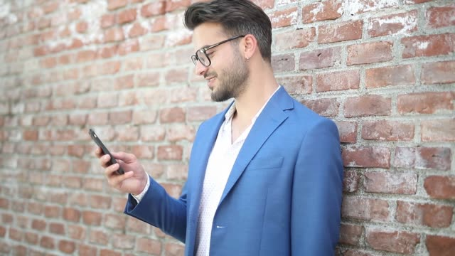 smart casual businessman leaning on a brick wall, writing a message on his phone, smiling and looking aside