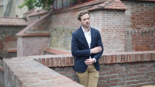 vídeos de stock, filmes e b-roll de empresário casual inteligente elegante apoiado em uma parede de tijolos, puxando a mão do bolso, cruzando os braços para o peito, e fixando sua jaqueta - braço humano