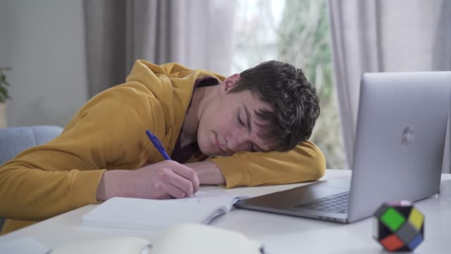 Video Smart Caucasian teenage boy getting asleep as writing in workbook. Portrait of exhausted college student studying hard indoors. Tiredness, overworking, education, lifestyle.