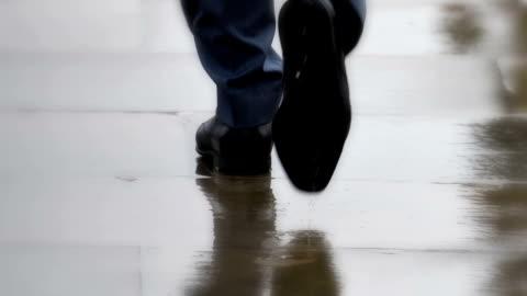 smarte stadtschuhe, geschäftsleute, die im regen spazieren gehen. nur füße, rückansicht. - geschäftsmann stock-videos und b-roll-filmmaterial
