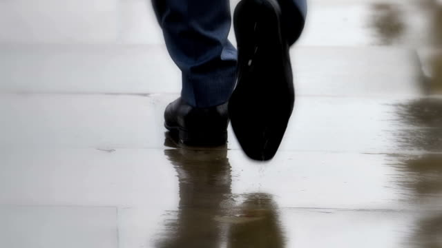 smart city shoes, businessmen walking in rain. feet only, rear view. - fare un passo video stock e b–roll