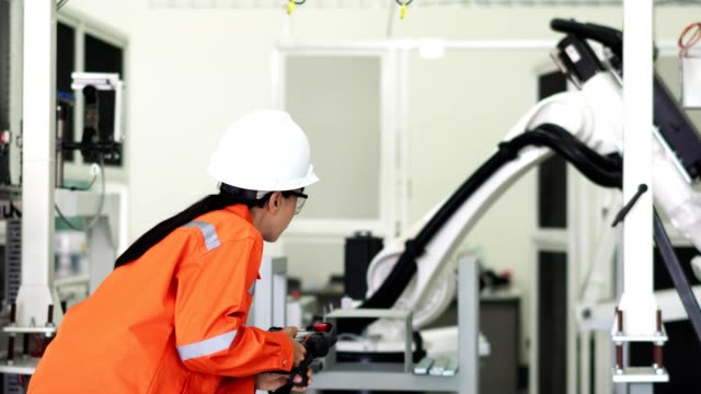 akıllı fabrika konsepti: profesyonel mühendis, üretim tesisinde endüstriyel robot ayarı el kumandası kullanır. - plant stem stok videoları ve detay görüntü çekimi