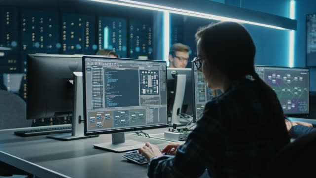 stockvideo's en b-roll-footage met slimme vrouwelijke it-programer werken op de desktop computer in data center systeemcontrole kamer. team van jonge professionals doen code programmeren - datacenter