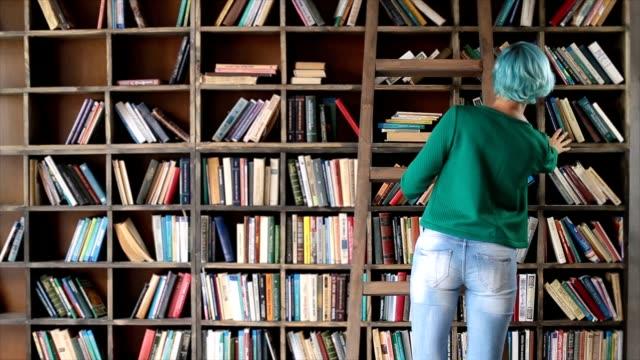 stockvideo's en b-roll-footage met slim meisje selecteren van literatuur boek in de winkel - boekenkast