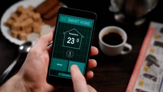 電話でスマート ホーム、アプリケーション。男は、スマート フォンから自宅のさまざまなパラメーターを管理します。スマート ホーム技術は、照明、温度、セキュリティ システムを制御することができます。 - コントロール点の映像素材/bロール