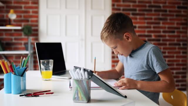 smart little boy does homework in her room - praca domowa filmów i materiałów b-roll
