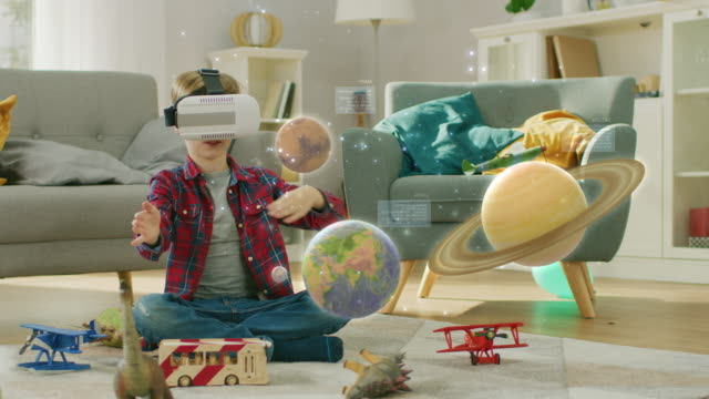 smart little boy wearing augmented reality headset plays with space learning software, with gestures he manipulates 3d planets, discovers facts about solar system and cosmos - studio camera video stock e b–roll