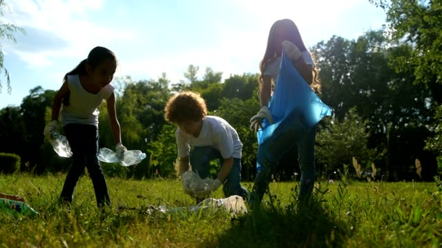 Smart little environmentalists putting plastic bottles in trash bags Taking care of mother earth. Adorable young volunteers spending free time outdoors and picking up empty plastic bottles while cleaning in park. sociology stock videos & royalty-free footage