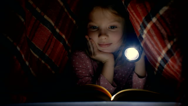 Smart Little Girl Reads Interesting Book with a Flashlight Under Blanket. video