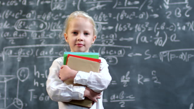 Smart Little Schoolgirl Posing Portrait shot with PAN of adorable little girl with blond hair holding books and posing against blackboard with complex calculus formulas genius stock videos & royalty-free footage