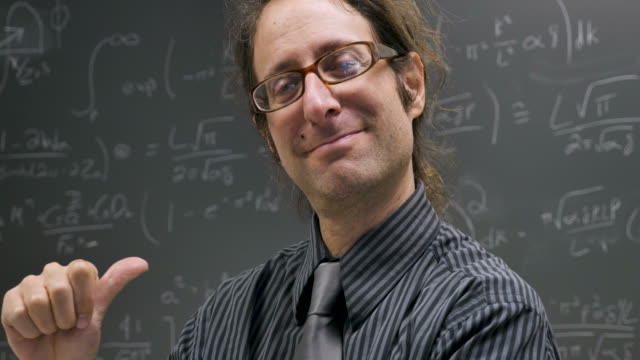 Smart male professor or scientist pointing at himself and then the chalkboard