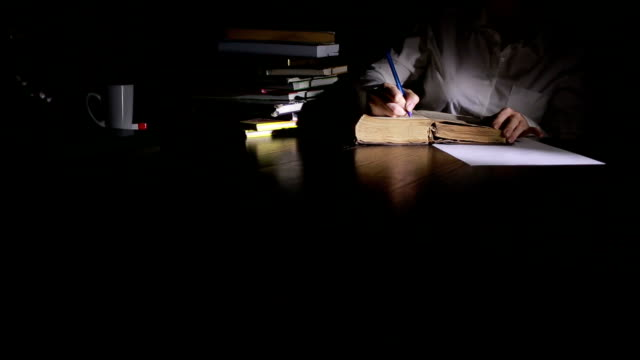 Smart man studying late at night, he is sitting at desk and reading book video