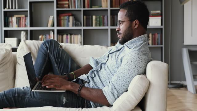 smart multiracial kerl arbeitet aus der ferne auf dem computer von zu hause. - online dating stock-videos und b-roll-filmmaterial
