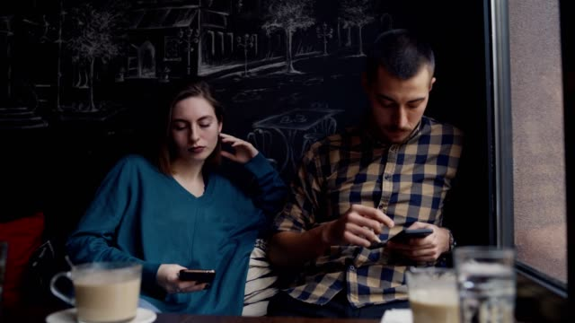 Smart phone addiction Young couple obsessed with social media ignoring each other in a cafe. ignoring stock videos & royalty-free footage