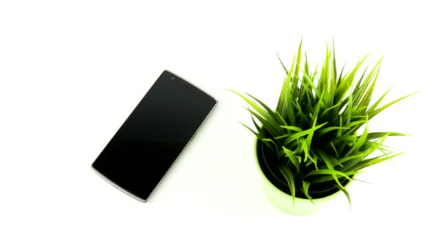 Smart Phone Next To Green Grass In Ceramic Pot Panning Movement