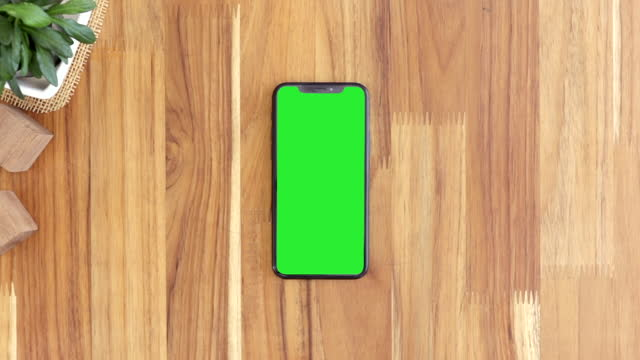 Smart phone on hand with green screen, Close-up the cell phone is on the brown wood desktop