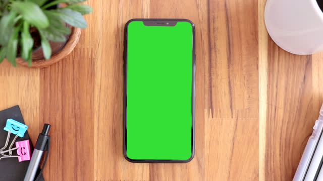 Smart phone on hand with green screen, Close-up the cell phone is on the brown wood desktop, Man's finger double touching display mobile phone with chroma key, Top view