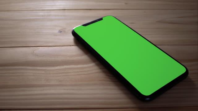 vídeos de stock e filmes b-roll de smart phone place on table wood , green screen telephone, zoom shoulder view. - mesa mobília
