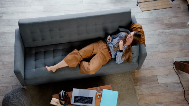 smart phone procrastination. young attractive caucasian woman lying down on sofa scrolling social network apps at home. - divano procrastinazione video stock e b–roll