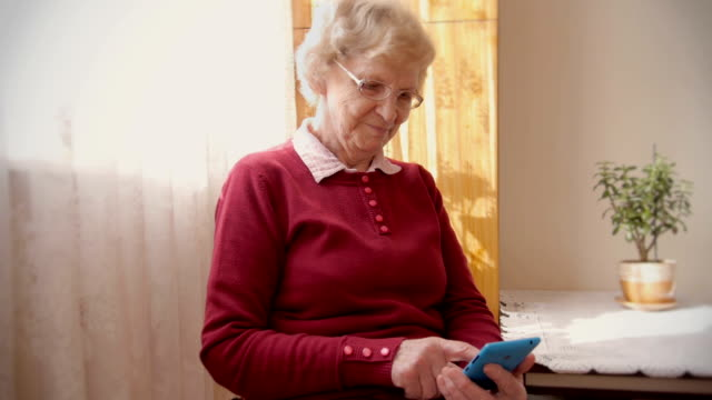 Smart Phone Senior Grandmother tapping buttons on her smart phone. grandmother stock videos & royalty-free footage
