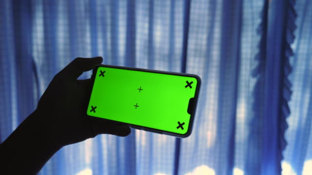Smart Phone with Green Screen on a Pillow in Bed Room with Sunlight Through Curtains