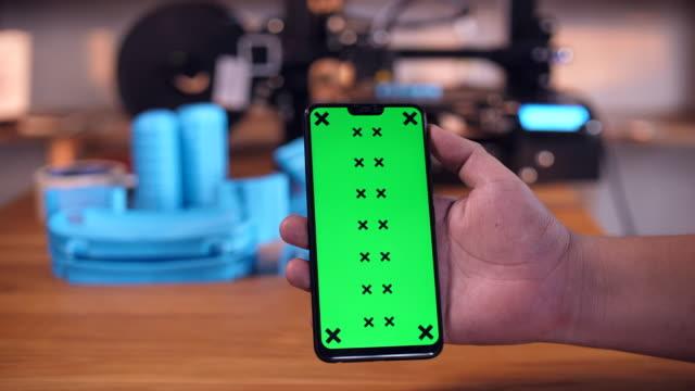 3Dプリンタラボラトリーの机の上に緑の画面を持つスマートフォン ビデオ