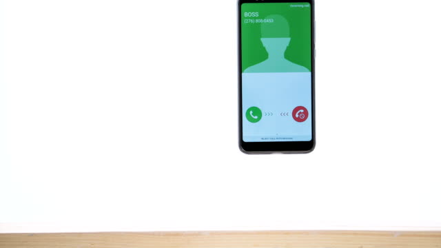 Smart phone with incoming boss call, stop motion, animation. Smart phone vibrates, bounces and flies up from the table.