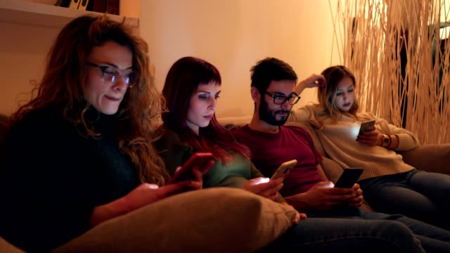Smart phones addiction Small group of friends sitting in living room, using smart phones and ignoring each others. group of people stock videos & royalty-free footage