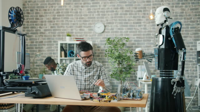 Smart robot bringing coffee to male engineer working in office, guy drinking
