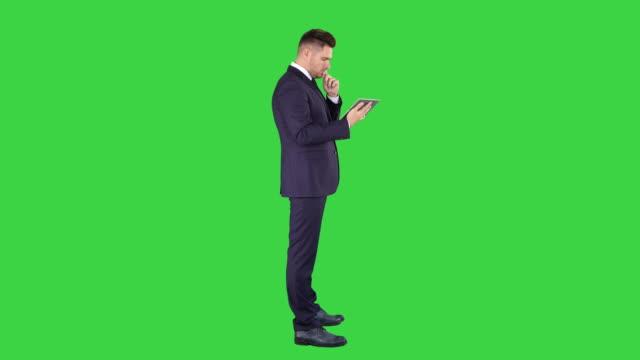 Smart senior businessman using a technology tablet on a Green Screen, Chroma Key