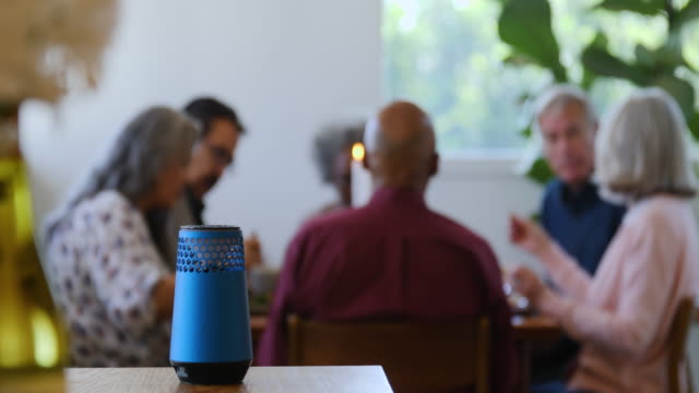 smart speaker on table with friends in background - assistente virtuale video stock e b–roll