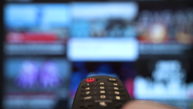smart tv and hand pressing remote control. tv screen channel surfing - television industry stock videos & royalty-free footage