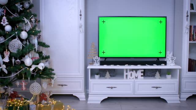 smart tv with green screen near christmas tree in living room - christmas movie video stock e b–roll