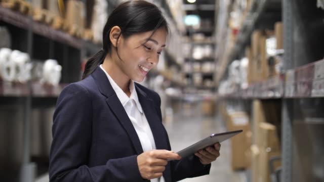 vídeos y material grabado en eventos de stock de gestión inteligente de almacenes: las mujeres asiáticas de negocios sostienen la tableta digital en el almacén - suministros escolares