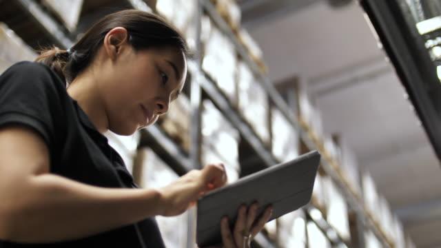 vídeos y material grabado en eventos de stock de gestión inteligente de almacenes trabajador de almacén usando la tableta digital para comprobar el stock y mirar la cámara - suministros escolares