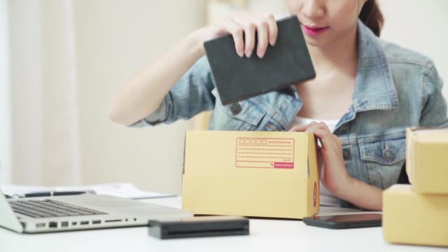smart young asian entrepreneur business woman owner of sme checking order on smartphone working at home. small business owner at home office concept. - owner laptop smartphone video stock e b–roll