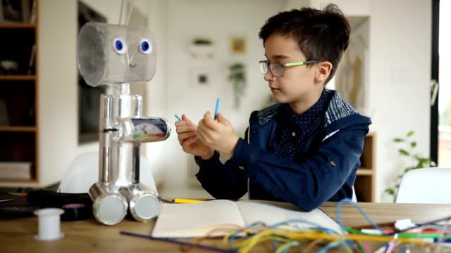 smart young boy engineer constructing a robot alone - манипулятор робота производственное оборудование стоковые видео и кадры b-roll