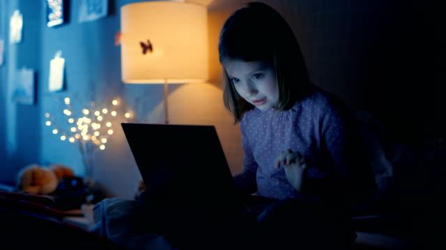 smart ung flicka i hennes sovrum sent på natten sitter på sängen med laptop och typer något intressant. hennes natt lampa är på. - digital reading child bildbanksvideor och videomaterial från bakom kulisserna