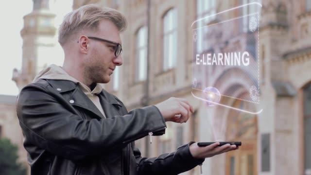 vidéos et rushes de intelligent jeune homme avec des lunettes montre un hologramme conceptuel e-learning - étudiant(e)
